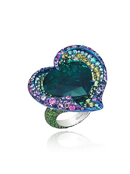 BE STILL MY HEART    This emerald and gem-set ring by CHOPARD was designed as a flower, set at the centre with a heart-shaped emerald weighing an eye-catching 19 carats. A colourful overlapping gemstone surround completes the artistry.